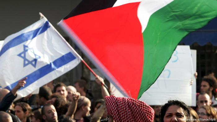 نشطاء سلام يحملون أعلام فلسطين وإسرائيل. Foto: dpa