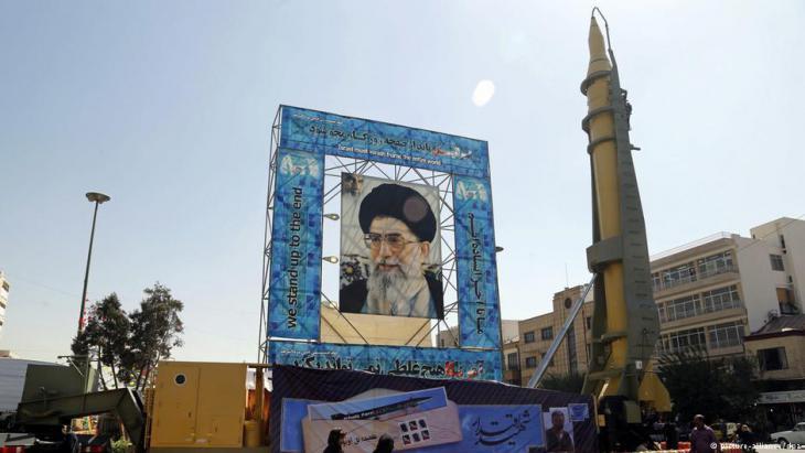 صورة الخامنئي وإلى جانبها صاروخ في إيران.