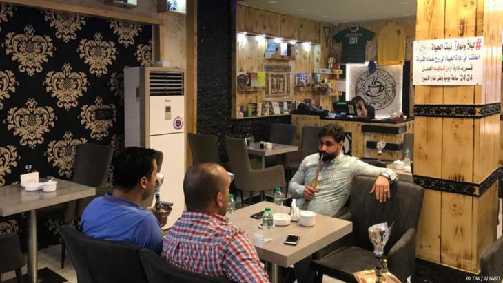 """العراق - مهرجان """"من الكرادة أختار الحياة"""" - بغداد تنفض غبار الموت - منطقة الكرادة البغدادية تعود زاهية إلى الحياة.مقهى لا تغلق أبوابها أبداً!: صاحب مقهى في الكرادة، سبق المهرجان بأن أعلن فتح المقهى لـ(24) ساعة في اليوم، أمام الزبائن، من دون إغلاق أبداً، وهي خطوة قال إنه يسعى من خلالها للمساهمة في """"إعادة الحياة للمنطقة التي أحبها، الكرادة"""".  ويشير  إلى أن المقهى في أول أيام الإعلان عن أوقات العمل الجديدة فيه، كان يمثل مفاجأة لجميع من يمر في وقت متأخر من الليل، بالقرب منه، حتى يدخل يحتسي شاياً فيقرأ الإعلان عن الأوقات، ويبدي لنا الثناء ويتفاعل مع الأمر بابتسامة، هي جل ما أرغب برؤيته على وجوه أهالي الكرادة والمارين فيها""""."""