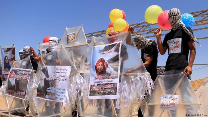 منطقة البُريج ، في قطاع غزة ، في الأراضي الفلسطينية - محتجون فلسطينيون يُحضِّرون بالونات وطائرات ورقية محملة بمواد قابلة للاشتعال، تُطَيَّر باتجاه إسرائيل على الحدود بين إسرائيل وغزة: البُريج وسط قطاع غزة بتاريخ 14 يونيو / حزيران 2018. (photo: Imago/ZUMA Press)
