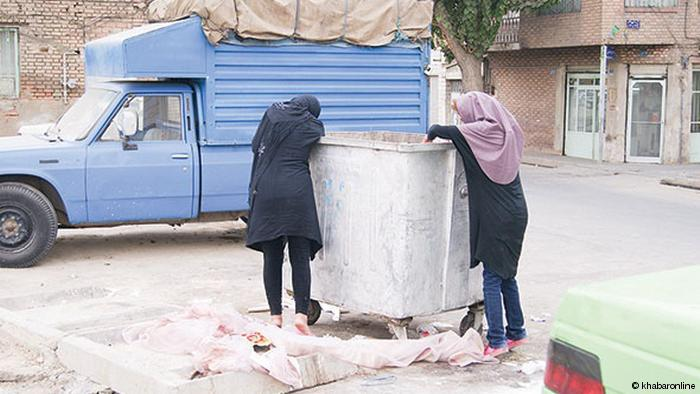 فتاتان تبحثان عما يمكن أحذه من برميل القمامة في طهران - إيران.