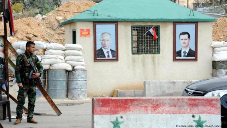 صورة الرئيس الروسي بوتين بجانب صورة بشار الأسد في نقطى تفتيش بالقرب من دمشق.
