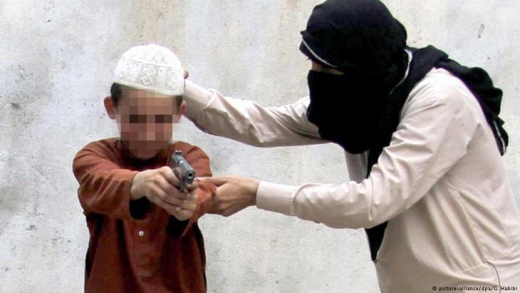 """رجل من تنظيم الدولة الإسلامية """"داعش"""" يدرب طفلا على القتال."""