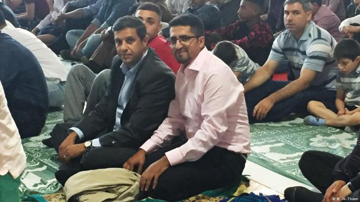رائد صالح (يسار في الصورة) أثناء صلاة عيد الفطر في أحد مساجد برلين: رائد صالح هو رئيس الكتلة البرلمانية للحزب الاشتراكي الديمقراطي SPD في مجلس نوَّاب ولاية برلين منذ عام 2011. ولد عام 1977 في فلسطين وقد جاء في طفولته إلى برلين.
