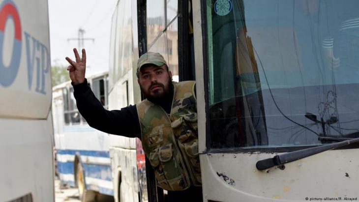 رجل يلوح بيديه من داخل باص قام بنقل مدنيين ومسلحين من الجيش السوري الحر يوم الثالث من مايو 2018 من مخيم اليرموك إلى محافظة إدلب.  Foto: picture-alliance/R. Alsayed