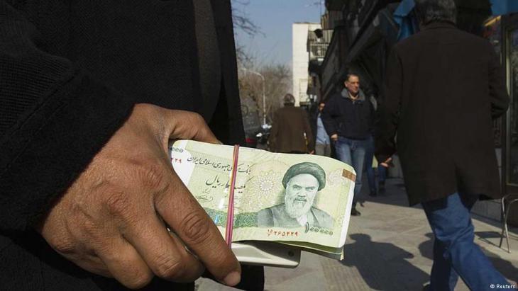 عملة ورقية إيرانية عليها صورة الخميني في يد أحد الأشخاص في الشارع – إيران.