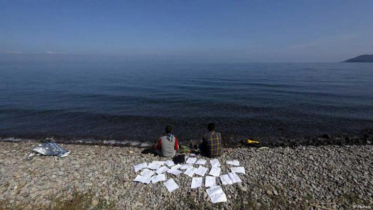 طالبان سوريان يقومان بتجفيف وثائقهما في شهر تشرين الأوَّل/أكتوبر 2015 على شاطئ في جزيرة ليسبوس اليونانية.  (photo: Reuters/Yannis Behrakis)