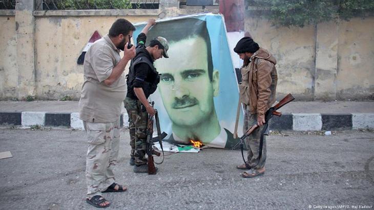 مقاتلون معارضون يحرقون صورة الأسد - سوريا.