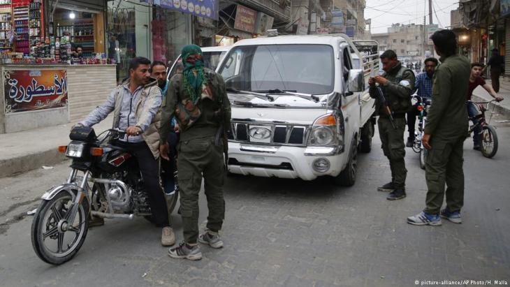 عناصر من قوات الأمن الداخلي الكردية تتحقق من أوراق هوية المدنيين السوريين في منبج، شمال سوريا، مارس / آذار 2018.  (photo: picture-alliance/AP Photo/H. Malla)
