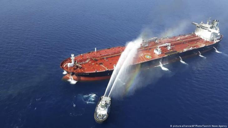 سفينة تابعة للبحرية الإيرانية ترش المياه لإخماد حريق على ناقلة نفط في بحر عمان - 13 حزيران / يونيو 2019.  (photo: picture-alliance/AP Photo/Tasnim News Agency)