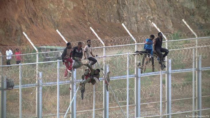مهاجرون أفارقة يصعدون السياج الحدودي الفاصل بين المغرب وجيب سبتة الإسباني في شمال إفريقيا.  (photo: Reuters/Reuters TV)
