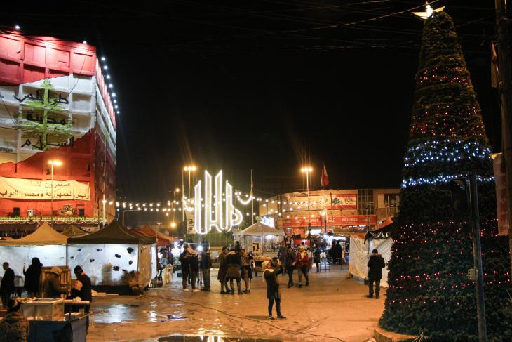 """بمدينة طرابلس اللبنانية شجرة عيد الميلاد في ساحة النور، بجانب كلمة """"الله"""" المكتوبة بحروف كبيرة مضاءة بألوان زاهية. Foto: Hanna Resch"""