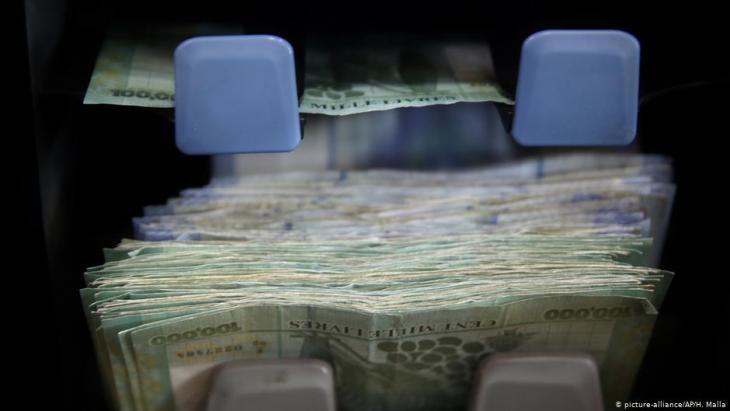 عَدُّ نقود بالعملة اللبنانية على آلة في أحد محلات صرف العملات في بيروت - لبنان.  (photo: AP Photo/Hussein Malla)