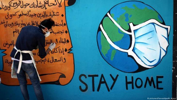 رسم جداري في غزة يطلب من الناس البقاء في المنازل في ظل جائحة كورونا.  Foto: picture-alliance/dpa/M.Ajjour