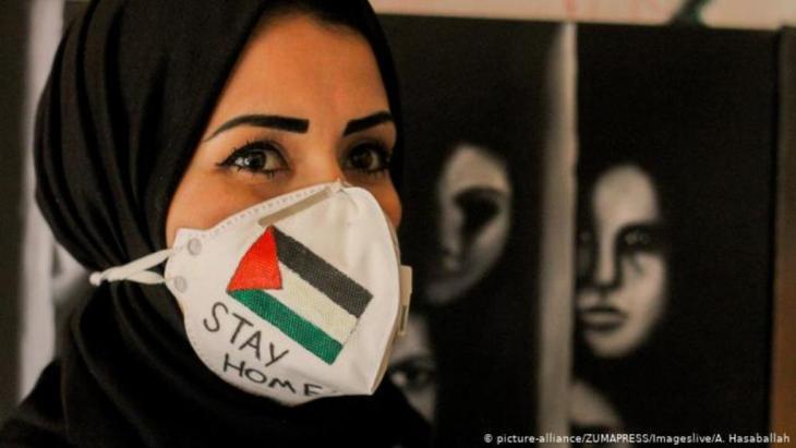 (picture-alliance/Zumapress/Imageslive/A.Hasaballah) صورة رمزية لسيدة في قطاع غزة تستعد لمواجهة فيروس كورونا