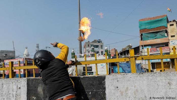 رجل يلقي زجاجة حارقة على مسجد في دلهي - الهند. (photo: Reuters/D. Siddiqui)