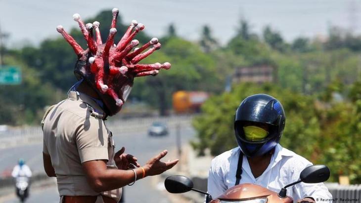 شرطي هندي يحذر من فيروس كورونا.