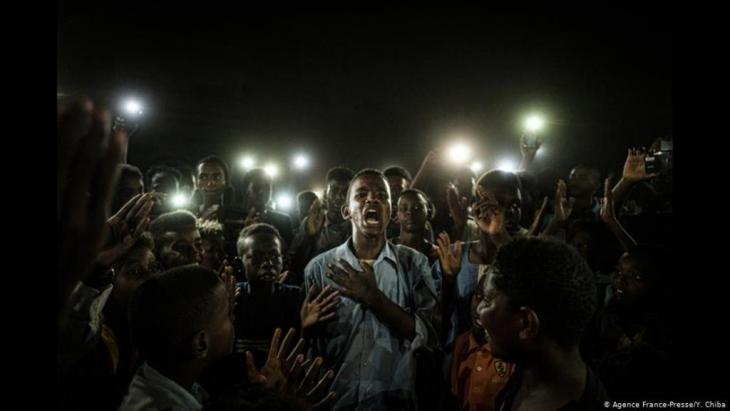صورة الشاب السوداني الفائزة بجائزة وورلد بريس فوتو 2020 وتُظهر شاباً سودانياً ثائراً محاطاً بشباب آخرين ينيرون ما حوله بهواتفهم النقالة. التُقطت الصورة خلال انقطاع الكهرباء في الخرطوم وسط الاحتجاجات ضد الرئيس السوداني السابق عمر البشير.