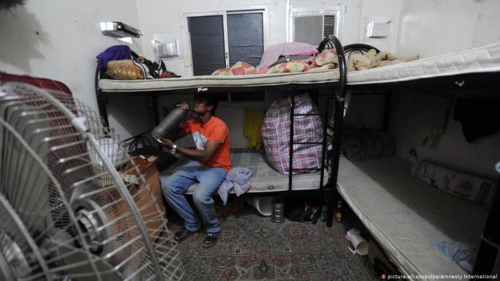 عامل وافد جالس في مسكنه - غرفة مشتركة مع آخرين - في قطر. Foto: dpa