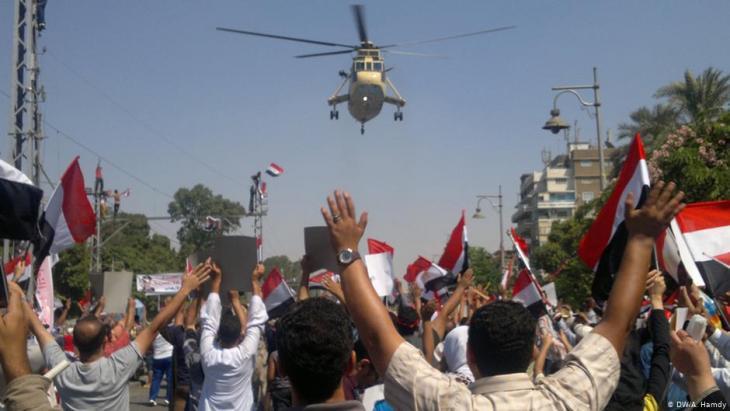 مصريون يهتفون في حي مصر الجديدة بالقاهرة لطائرة مروحية عسكرية محلِّقة في يوليو 2013. Foto: DW/A.Hamdy
