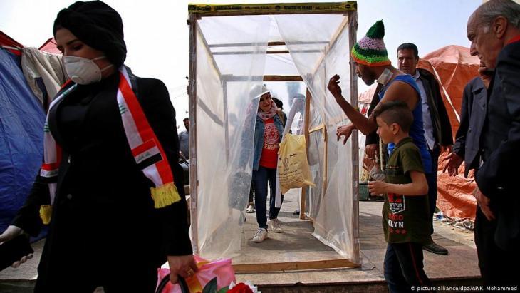 محتجون عراقيون يمرون عبر حجيرة تعقيم ضد كورونا بنوها بأنفسهم.  Foto: picture-alliance/dpa/AP/K. Mohammed