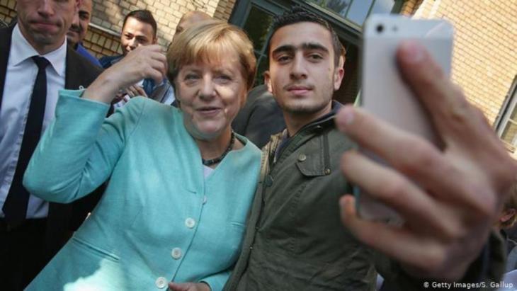 """صورة """"سيلفى"""" التقطها اللاجئ السورى، أنس مدامنى، جمعته بالمستشارة الأملانية أنجيلا ميركل. (Getty Images/S. Gallup"""