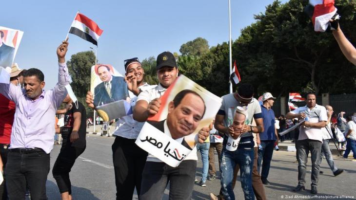 """مصر تبدأ التصويت لانتخاب برلمان جديد. أنصر السيسي يحملون ملصقات """"تحيا مصر""""."""