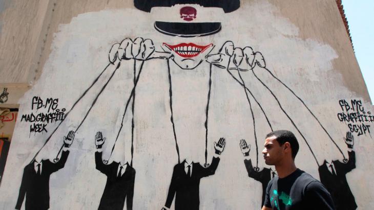 رسم جداري قرب ميدان التحرير في القاهرة في مصر يُظهِر أن الجيش يتحكم بخيوط كل شيء في البلاد.  (photo: Reuters)