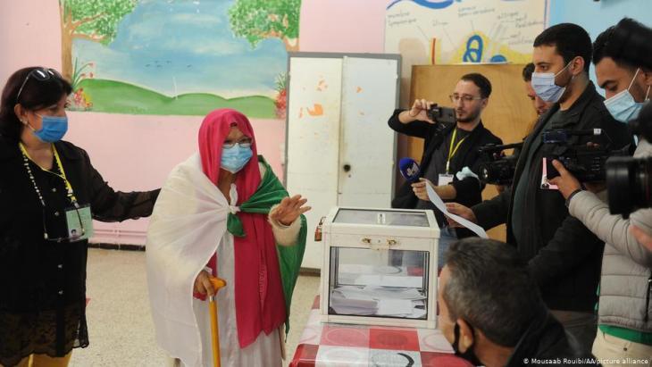 سيدة مسنة ملفوفة بالعلم الجزائري تدلي بصوتها في الاستفتاء على الدستور الجزائري في 1 نوفمبر / تشرين الثاني 2020.  (photo: Mousaab Rouibi/AA/picture-alliance)