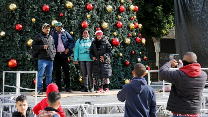 مسيحيون فلسطينيون يلتقطون صورا تذكارية أمام شجرة عيد الميلاد 2020 في بيت لحم.