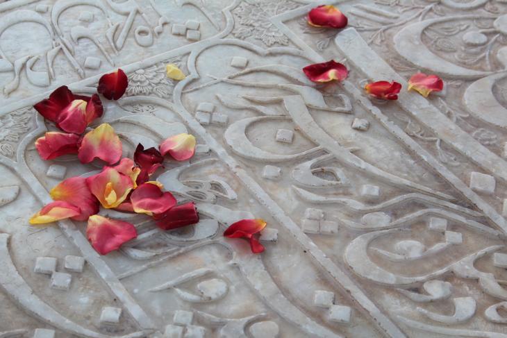 القبر الرخامي للشاعر حافظ وأوراق ورد أحمر نثرها عليه أحد الزوار – إيران.