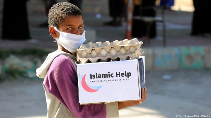 طفل يمني ذو أصل إفريقي يحمل مساعدات غذائية في مدينة تعز - اليمن. Foto: Getty Images/AFP/A.Al-Basha