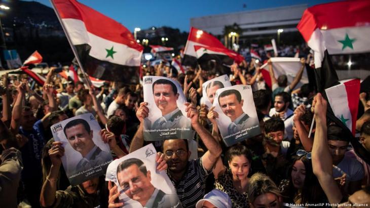ابتهاج بعض الناس بصورة رئيس النظام السوري بشار الأسد. Foto: Hassan Ammar/AP Photo/picture-alliance