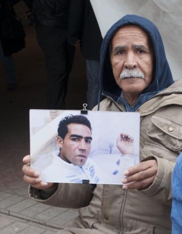 محمد ممسك بصورة ولده القتيل أثناء مظاهرة لأقرباء ضحايا الثورة في تونس. Foto: Sarah Mersch