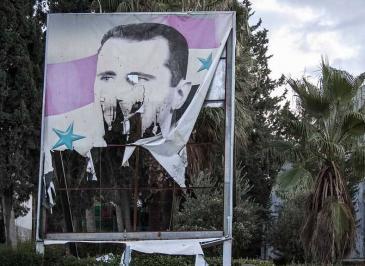 صورة ممزقة لبشار الأسد في مدينة حلب شمال سوريا. Foto: AP