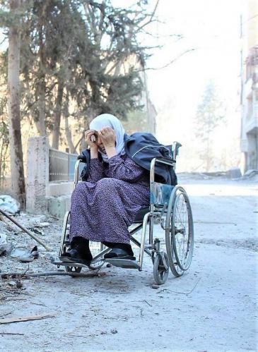 امرأة سورية على كرسي متحرك في مناطق قصف النظام السوري. الصورة عن طريق منصور حسنو