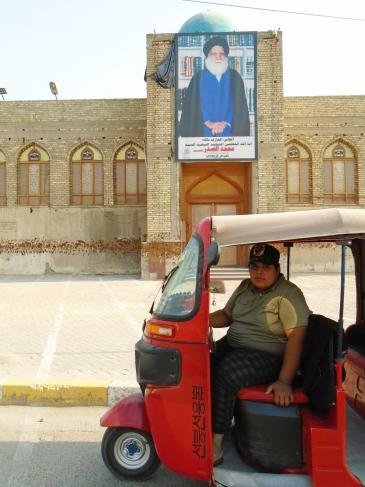 حسين يجلس بثقة في توك توك ذي لون أحمر ناري بغداد - العراق. Foto: Birgit Svensson
