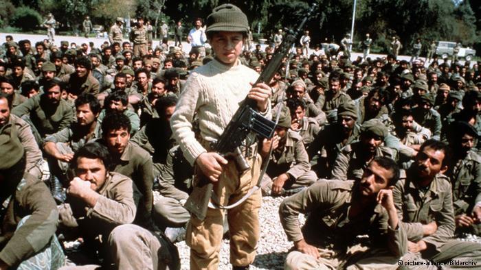 جندي إيراني صغير السن يرفع بندقية جي سي إيرانية الصنع أمام الكاميرا ويحيط به مئات الأسرى العراقيين من سنوات الحرب.