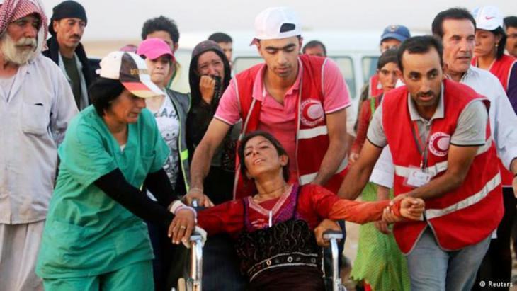 بعض المتطوعين الأكراد في منظمة الهلال الأحمر يقدمون الإسعافات الأولية للاجئين الأيزيدين