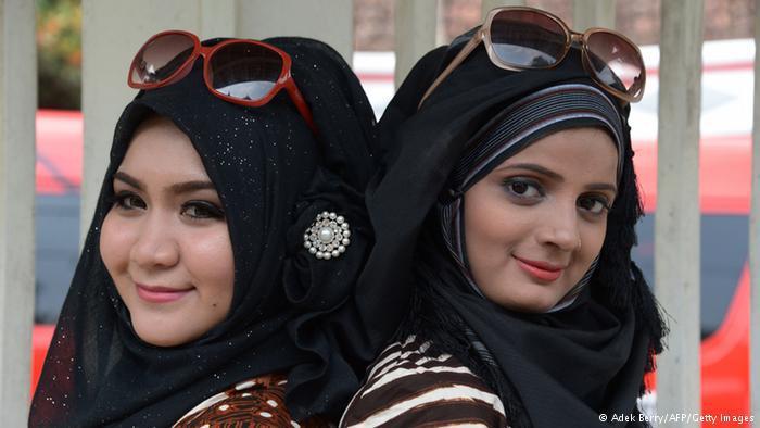 متسابقة هندية وأخرى ماليزية ترتديان العباءة الخليجية.