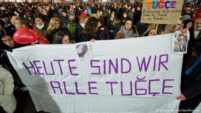 """قام الأشخاص المتجمهرون أمام مستشفى سانا-كلينيكوم في مدينة أوفنباخ الألمانية حيث كانت ترقد توتشه برفع لافتات كتبوا عليها """"كلنا اليوم توتشه""""."""