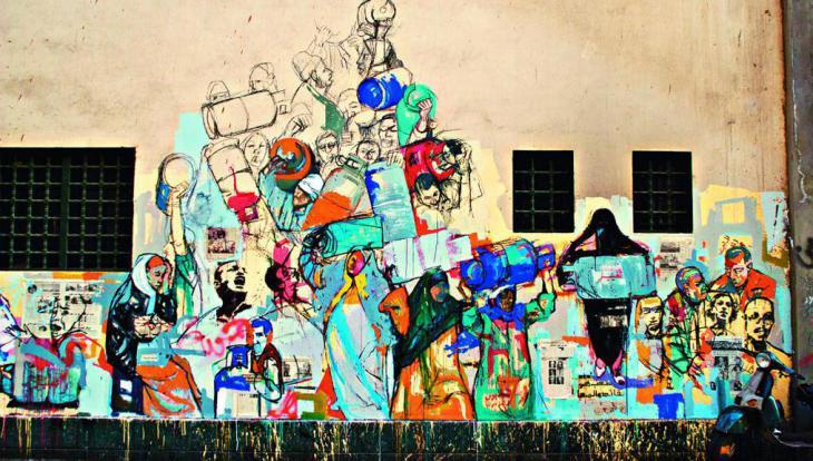 """ويقول مؤلف الكتاب عن هذا الرسم للفنانة هناء الديغم """"إنه يصور المشابهة بين طابور الانتخابات البرلمانية وطابور الحصول على الغاز والاشتباكات بين المواطنين بسبب ذلك""""."""