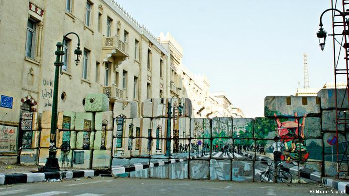 """ورسم الفنانون في حملة """"لا جدران"""" فوق الحواجز التي أغلقت الشوارع لحجب المتظاهرين، كما هو الحال قرب وزارة الداخلية. رسوم للفنان عمار أبو بكر مع فريق عمل مشترك."""