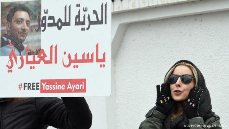 """""""يسقط يسقط قاضي العسكر"""" هو الشعار الذي واجه به متعاطفون مع المدون التونسي ياسين العياري قرار المحكمة العسكرية في تونس تخفيض عقوبة سجنه إلى 6 أشهر بتهمة الإساءة للجيش التونسي."""