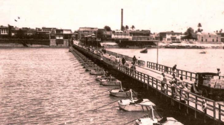 جسر الأئمة عام 1939، كان يُحمَل على زوارق ويصل بين منطقتي الكاظمية والأعظمية. حقوق الصورة: http://www.blackwhite.alnomrosi.net/Iraq/Baghdad/Baghdad100.htm و   https://ar.wikipedia.org/wiki/ملف:جسر_الأئمة_1939.jpg