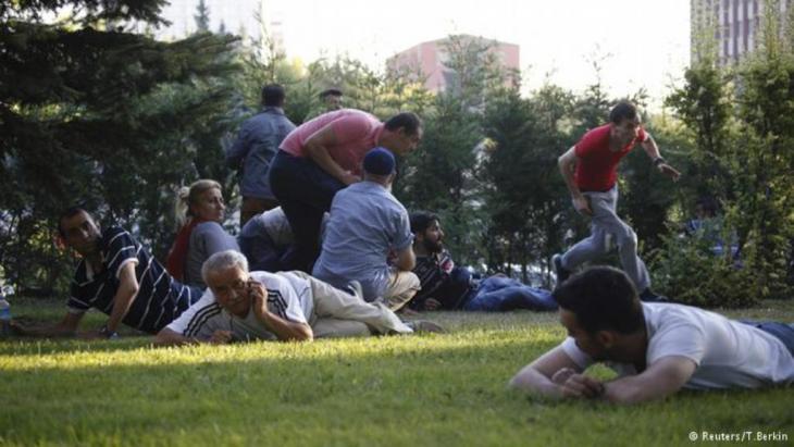 هزت انفجارات وأصوات إطلاق النار اسطنبول والعاصمة أنقرة في ليلة اتسمت بالفوضى بعد أن سيطر جنود على مواقع في المدينتين. كما استمر سماع دوي الانفجارات وإطلاق النار. في الصورة محتجون على الانقلاب يحمون أنفسهم في أحد ميادين أنقرة إثر سماعهم صوت الرصاص.