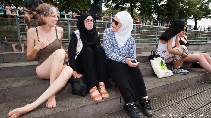 هؤلاء النساء الشابات برهن على أن المشاركة في حفل صيفي لا تحتاج إلى العري أو لباس الشاطئ. فالواحدة لفت نفسها في قطعة قماش والأخرى وضعت النقاب وثالثة غطت رأسها.