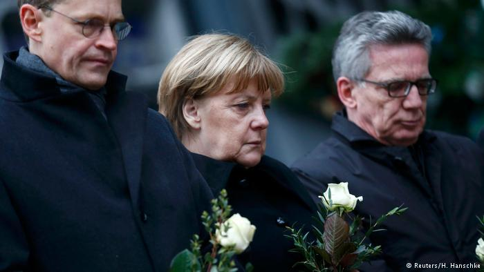 المستشارة الألمانية أنغيلا ميركل وأعضاء في حكومتها يضعون ورودا في مكان الحادث الذي شهد مقتل 12 شخصا وجرح 50 آخرين بسبب دهس شاحنة لحشد من الناس في أحد أسواق عيد الميلاد بالعاصمة الألمانية برلين.
