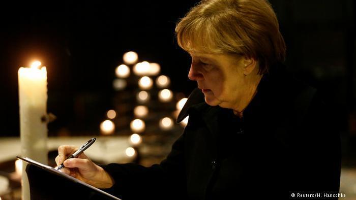 المستشارة الألمانية أنغيلا ميركل توقع في سجل خصص للعزاء في ضحايا هجوم الدهس.