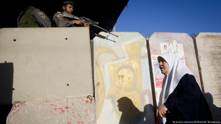 امرأة فلسطينية تمر في شهر رمضان في نقطة تفتيش قالنديا للصلاة في المسجد الأقصى.